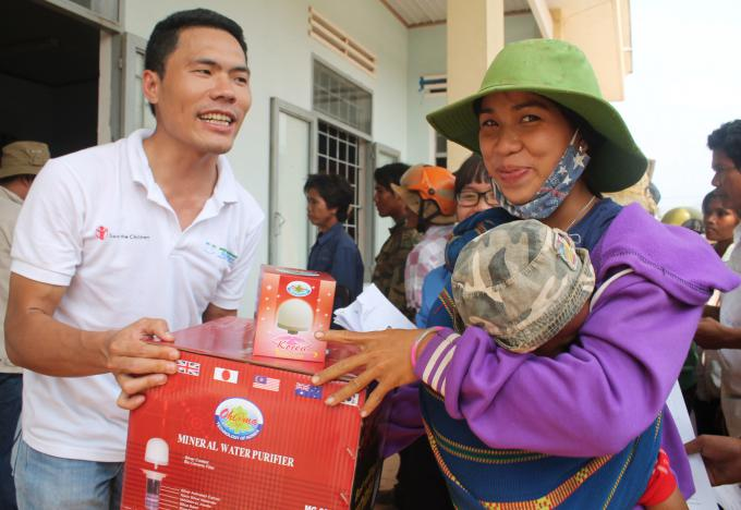 SC in Vietnam staff Tran Duc Manh (left) distributes water filters to a local resident in HBong commune, Chu Se district, Gia Lai province in the Central Highlands.